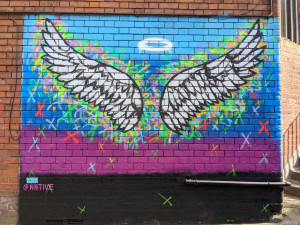 Angel wings and halo spray painted onto a wall
