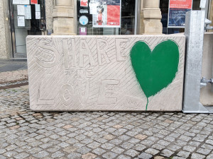 Concrete block with the phrase Share the Love carved into it with a heart shape painted green